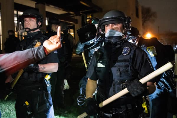 A protestor holds up a middle finger in defiance to riot police. Protestors and City of Brooklyn Center Police Officers clash outside the Brooklyn Center Police Department in Brooklyn Center, near Minneapolis after the death of Daunte Wright by police. (Credit Image: © imageSPACE via ZUMA Wire)