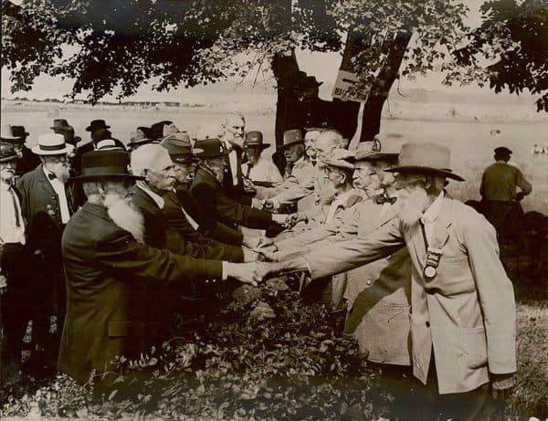 Union and Confederate veterans shake hands on the Gettysburg battlefield to mark the 50-year anniversary of the battle.